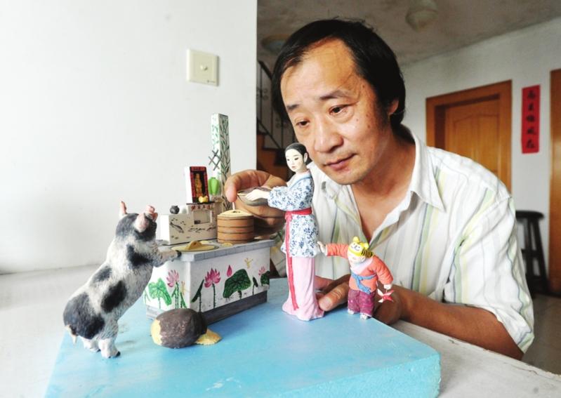 昨天,王开亚在对泥人彩绘作品《宠猪举灶》进行最后修饰。  □记者 杭兴微